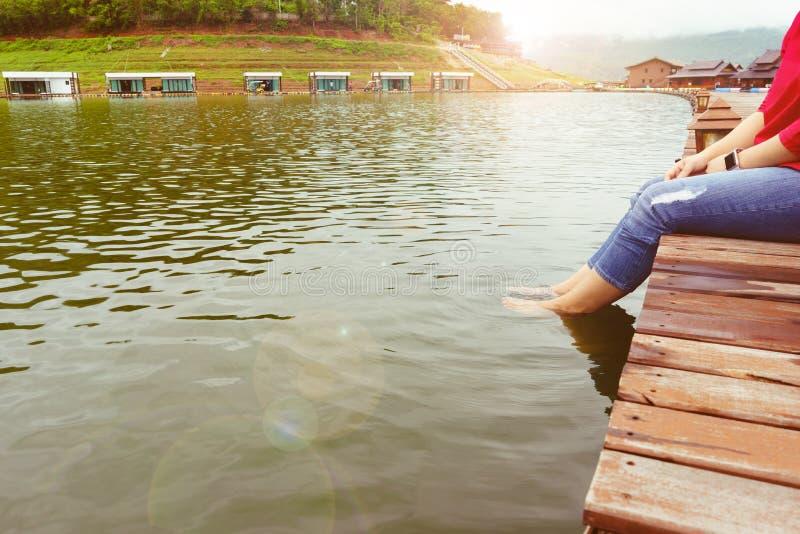Pés fêmeas no cais perto da margem dos bungalows fotos de stock royalty free