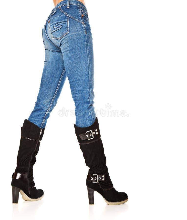 Pés fêmeas no calças de ganga e carregadores elevados imagens de stock