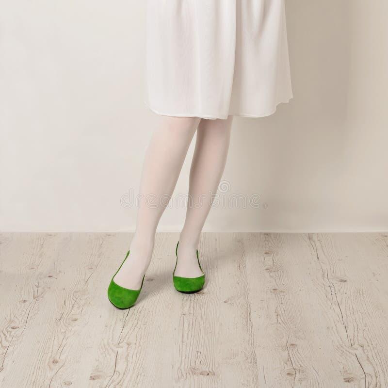 Pés fêmeas nos planos brancos das calças justas, da saia e do bailado em um b branco fotos de stock royalty free