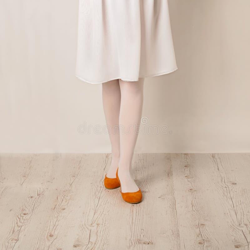 Pés fêmeas nos planos brancos das calças justas, da saia e do bailado em um b branco imagens de stock