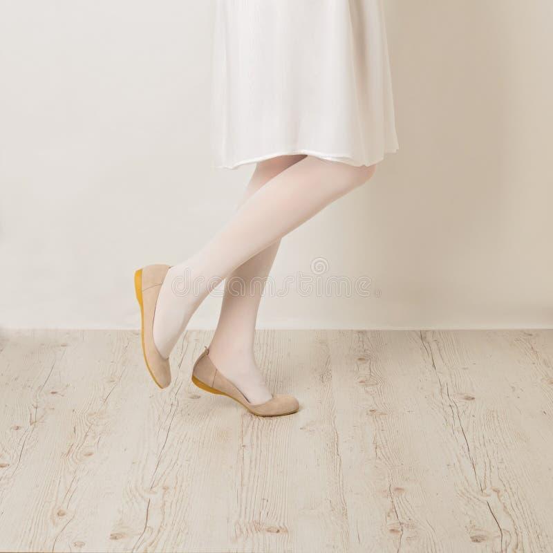 Pés fêmeas nos planos brancos das calças justas, da saia e do bailado em um b branco fotografia de stock