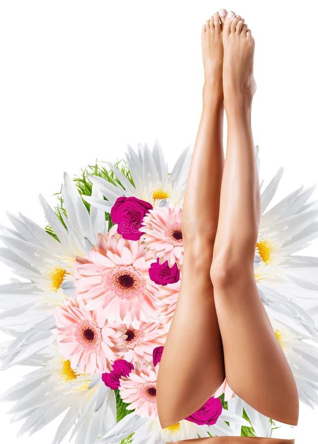 Pés fêmeas perfeitos sobre o ramalhete grande da flor imagem de stock royalty free