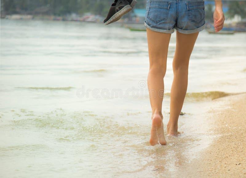 Pés fêmeas que andam na água imagem de stock