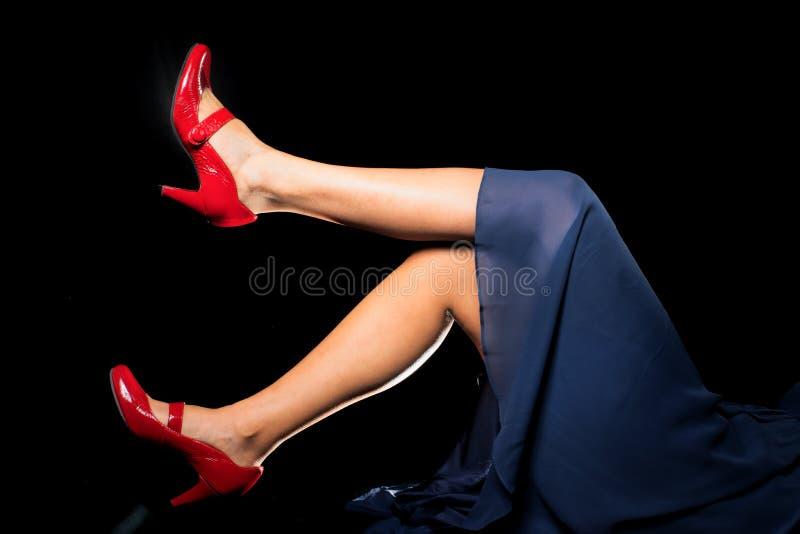 Pés fêmeas 'sexy' com sapatas vermelhas & o vestido azul foto de stock