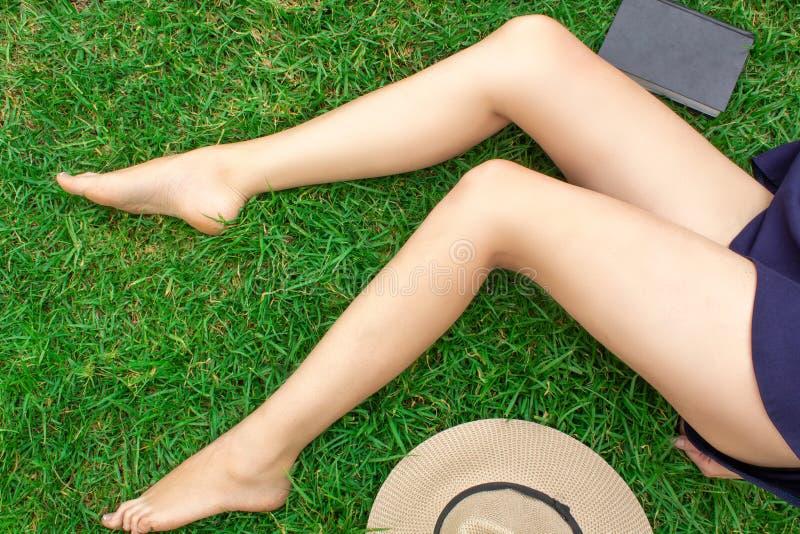 Pés fêmeas 'sexy' magros longos bonitos que encontram-se na grama Ao lado do chapéu e do livro foto de stock