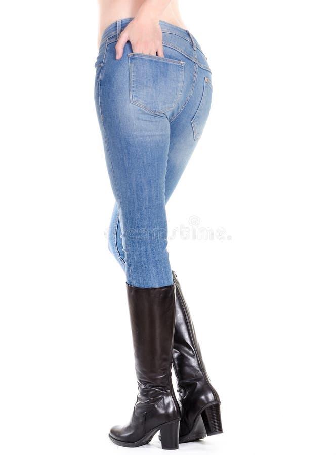 Pés fêmeas 'sexy' nas calças de brim com botas imagens de stock royalty free