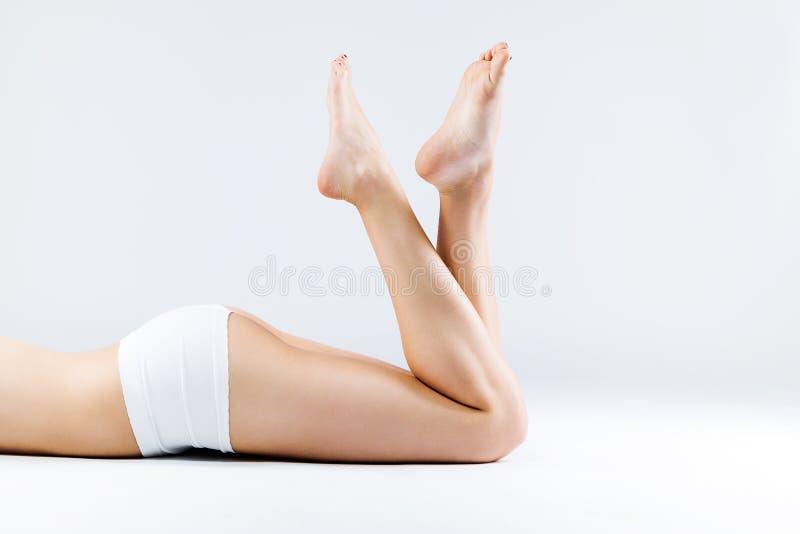 Pés lisos e encerados perfeitos da mulher com os pés que apontam acima imagens de stock