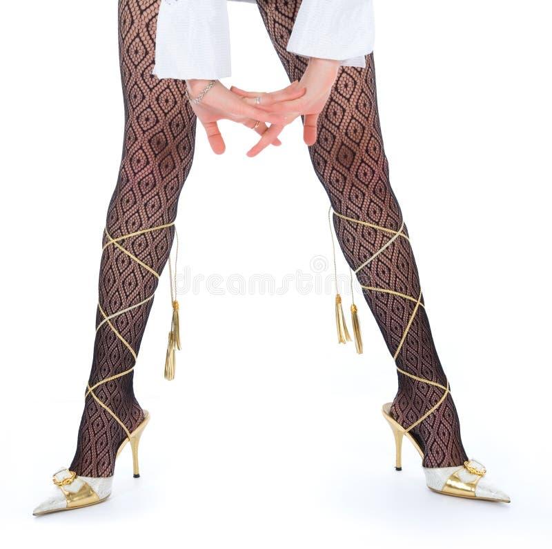 Pés longos da mulher nos dança-deslizadores brancos imagens de stock