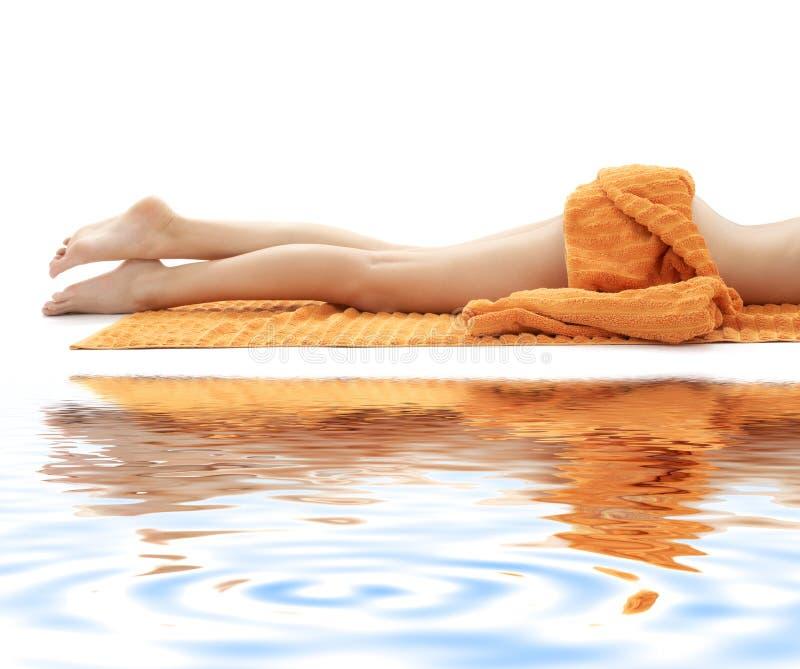 Pés longos de senhora relaxed com a toalha alaranjada no whi fotos de stock royalty free