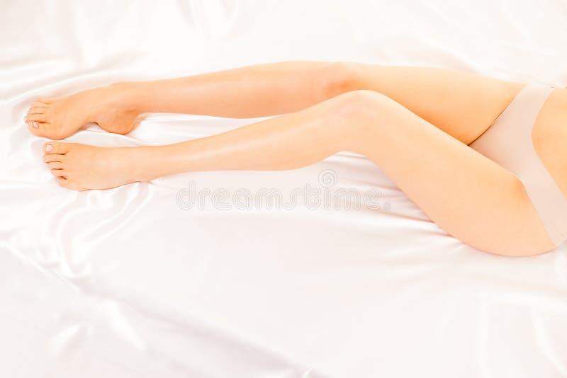 Pés longos e magros da mulher nas folhas brancas na cama fotos de stock royalty free