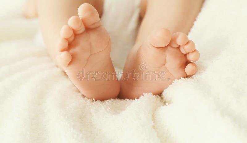 Pés macios do bebê do conforto do close up da foto na cama fotos de stock