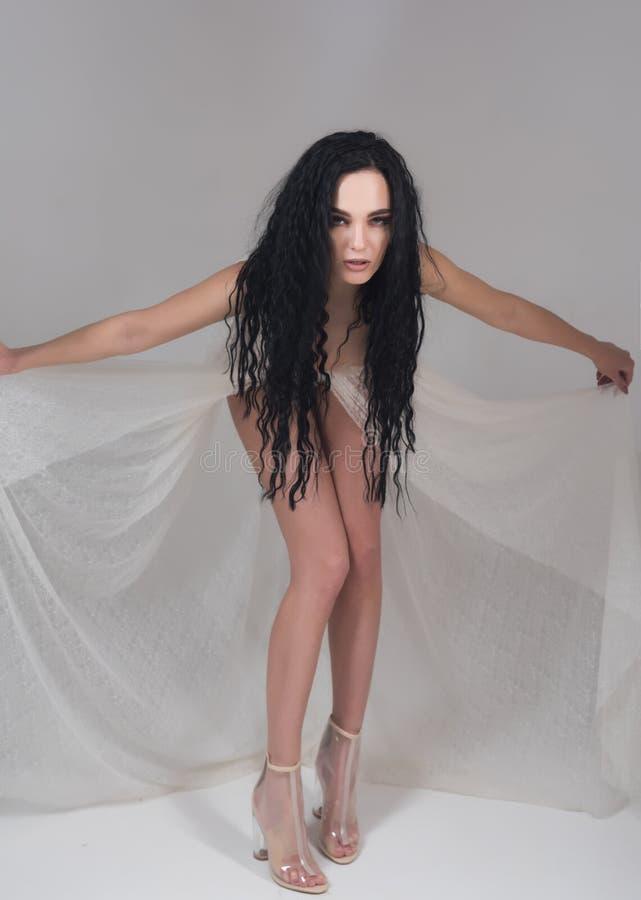 Pés magros conceito magro dos pés a mulher com cabelo moreno longo mostra-lhe os pés magros a menina tem os pés bonitos magros el fotografia de stock