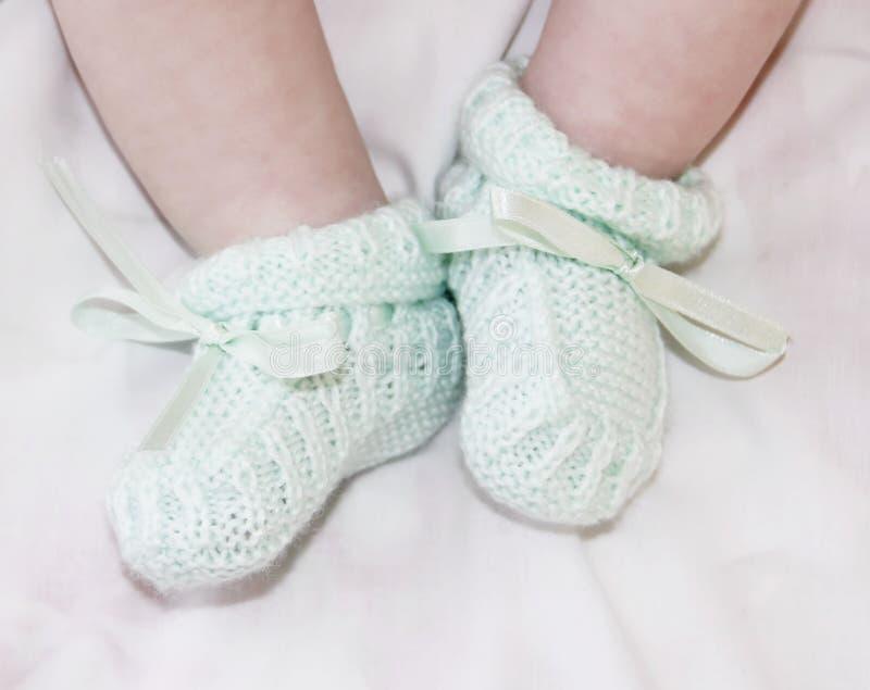 Pés minúsculos do bebê no sapatinhos de lã foto de stock