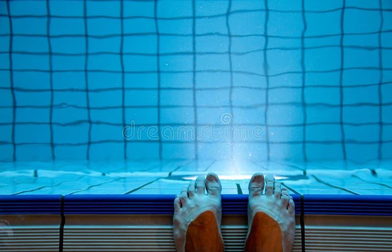 Pés na piscina interna imagens de stock royalty free