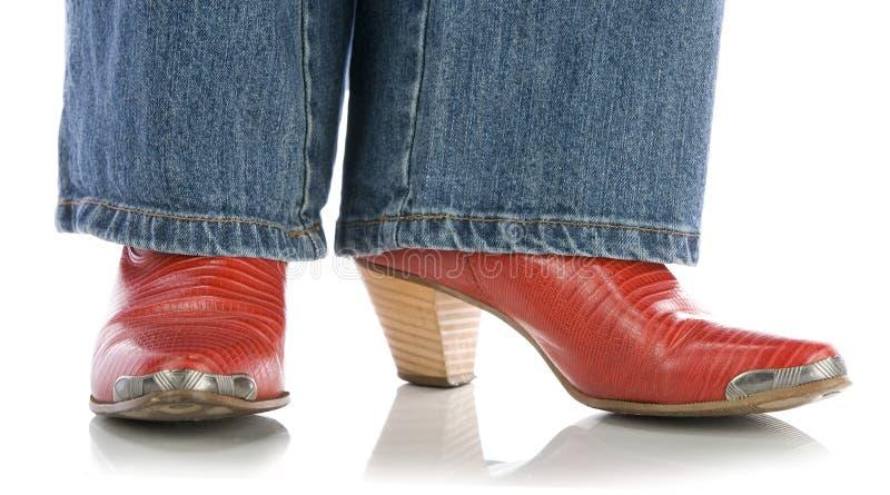 Pés nas calças de brim que desgastam carregadores de cowboy vermelhos no branco imagens de stock