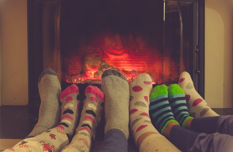 Pés nas peúgas de toda a família que aquece-se pelo fogo acolhedor foto de stock