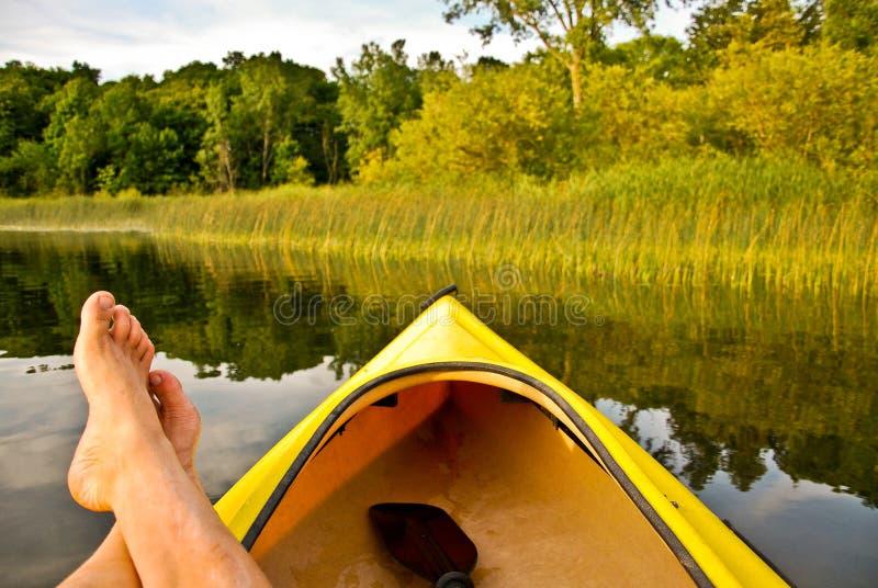 Pés no barco no lago imagens de stock