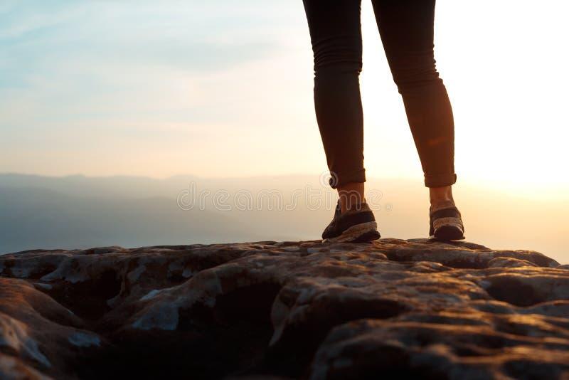 Pés novos irreconhecíveis na rocha do pico de montanha, vista traseira do caminhante da mulher do sucesso Conceito que consegue o imagens de stock royalty free