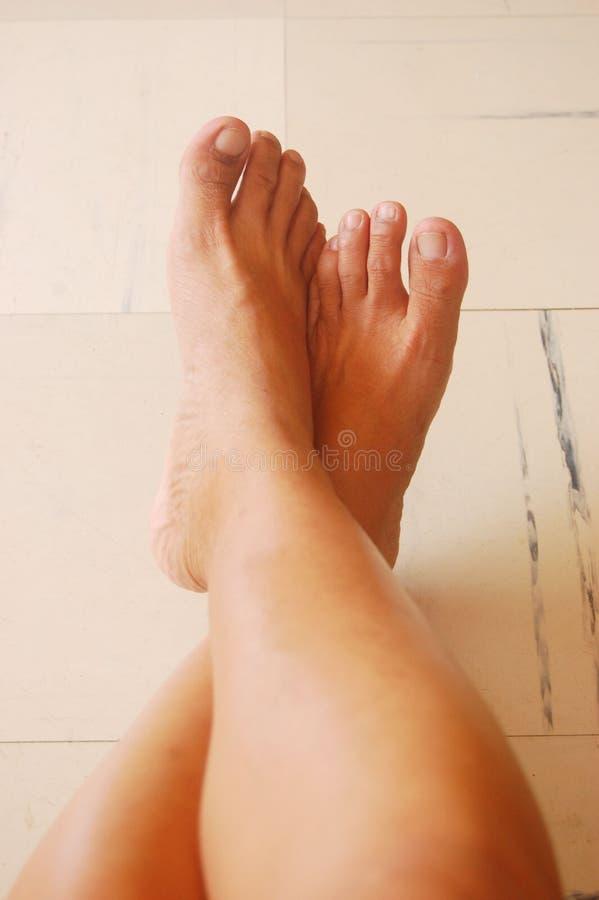 Pés ou pés dobrados no assoalho fotografia de stock royalty free