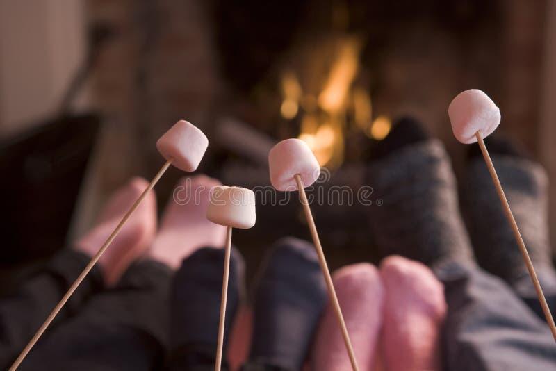 Pés que aquecem-se em uma chaminé com marshmallows imagem de stock
