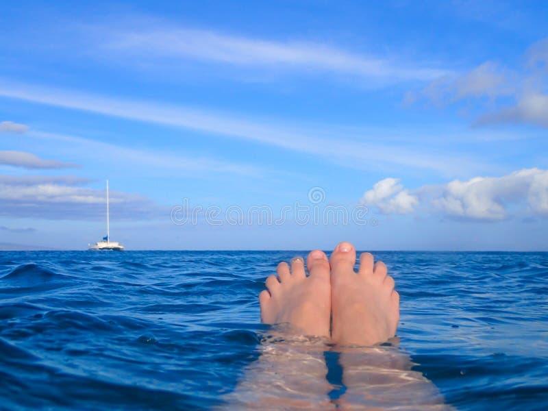 Pés que flutuam na superfície do mar com o barco no horizonte sob o azul fotos de stock royalty free