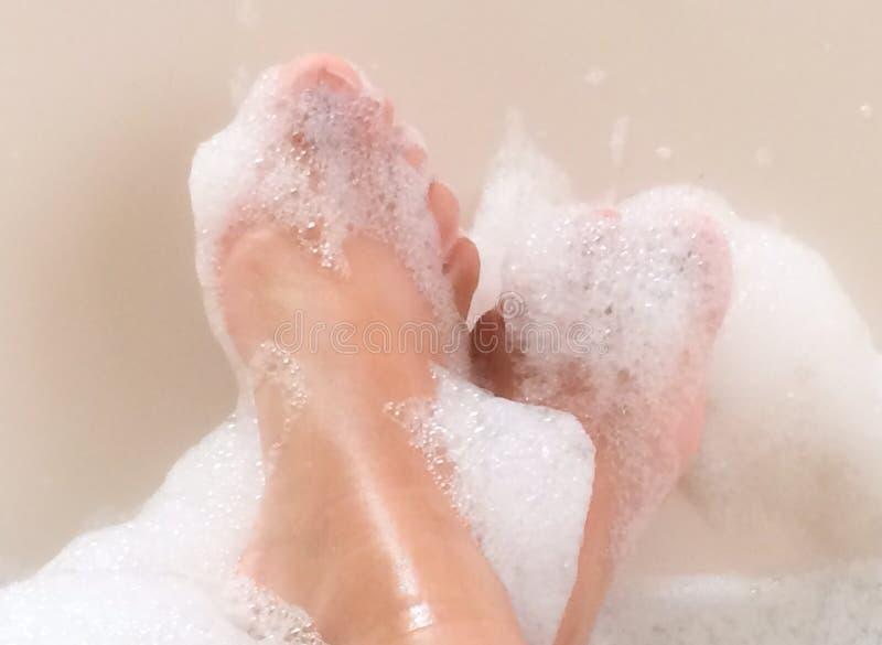 Pés que relaxam na cuba de banho de espuma ensaboada fotografia de stock royalty free