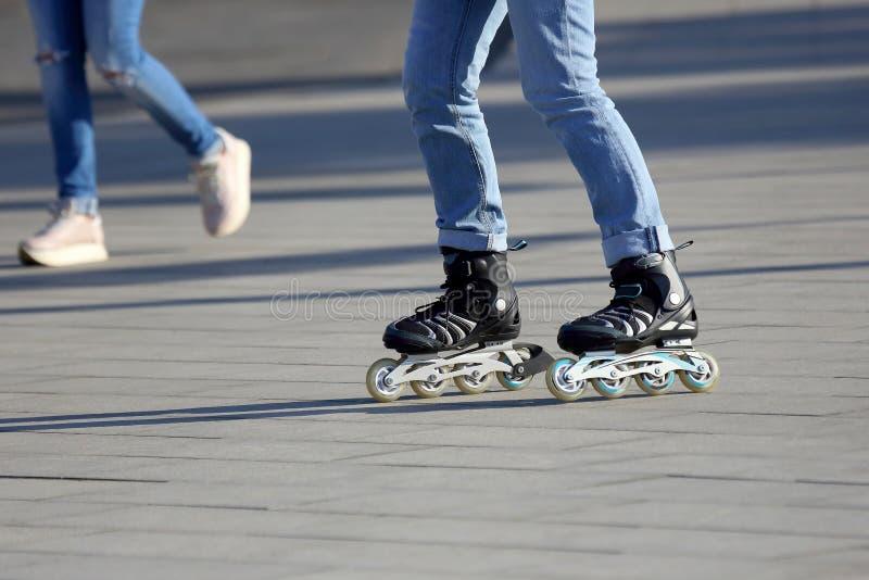Pés que rolam ao redor em patins de rolo no fundo p de passeio fotografia de stock
