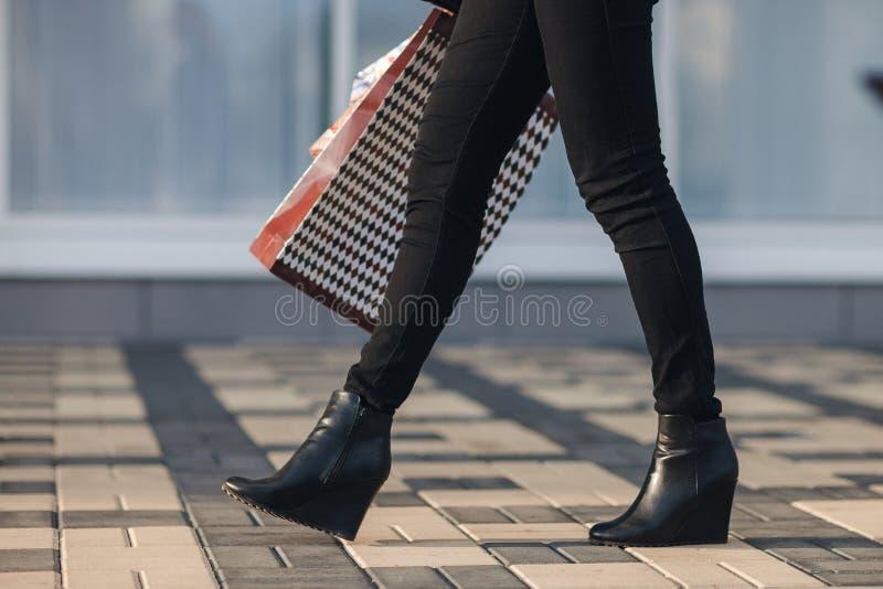 Pés 'sexy' da mulher em sapatas pretas da plataforma e em calças de brim pretas com os sacos de compras que andam na rua urbana d foto de stock royalty free