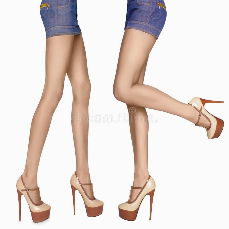 Pés 'sexy' longos da mulher pés fêmeas da beleza nos saltos altos skir das calças de brim imagens de stock