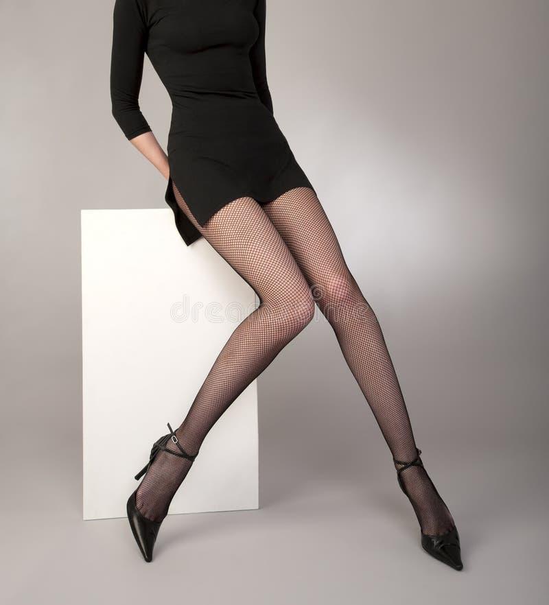 Pés Shapely das meninas com as calças justas pretas do fishnet fotos de stock royalty free