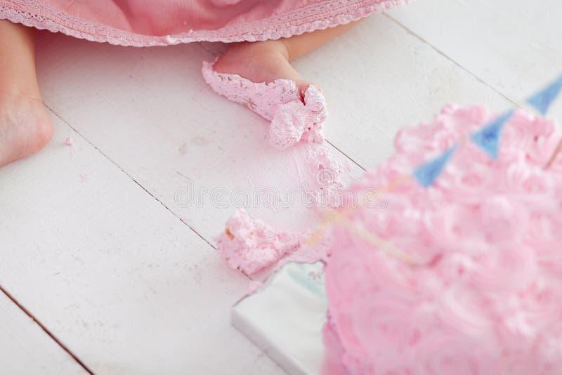 Pés sujos do bebê no fundo de madeira branco do assoalho, primeira quebra do bolo de aniversário fotos de stock royalty free
