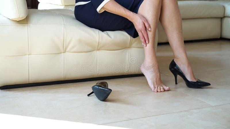 Pés tocantes da mulher de negócio com mão Opinião inferior colhida do retrato da vista lateral dos pés do ` s da mulher e de sapa fotografia de stock royalty free