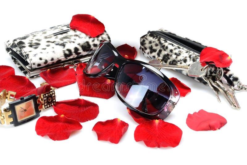 Pétalas cor-de-rosa vermelhas, acessório do ` s das mulheres, óculos de sol, relógio, carteira, chaves na vida imóvel em um fundo imagem de stock