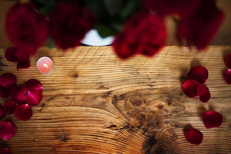 Pétalas cor-de-rosa vermelhas leves na madeira rústica fotos de stock royalty free
