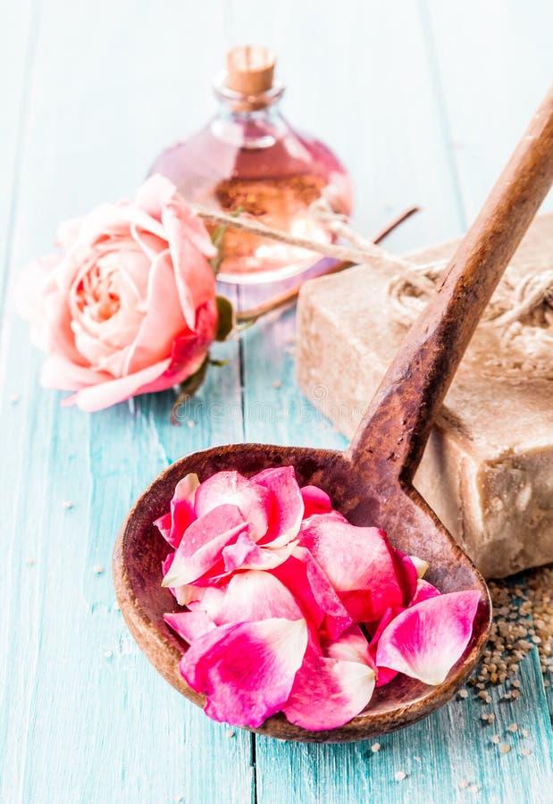 Pétales dans la poche en bois avec du savon, Rose rose et l'huile images stock