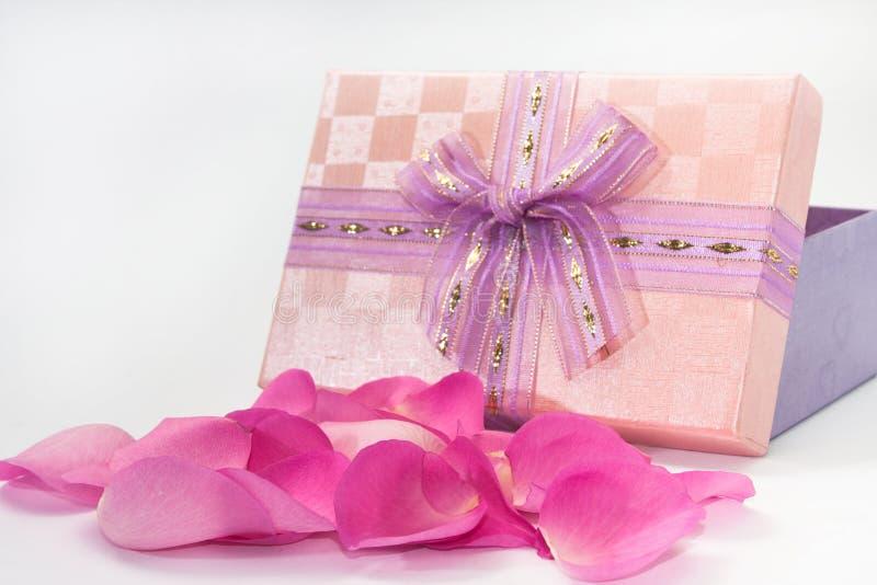 Pétales de rose roses devant la boîte rose avec le ruban photographie stock libre de droits