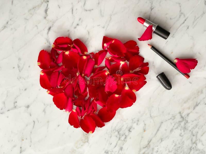 Pétales de rose rouges dans la forme de coeur avec le rouge à lèvres rouge sur le fond de table de marbre, vue supérieure Idées d photo libre de droits