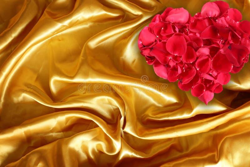 Pétales de rose sur la soie brune d'or de tissu photographie stock