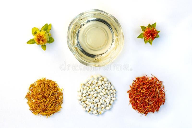 Pétales, inflorescences, graines et pétrole secs jaunes et rouges de carthame sur un fond blanc Vue de ci-avant Configuration pla image stock