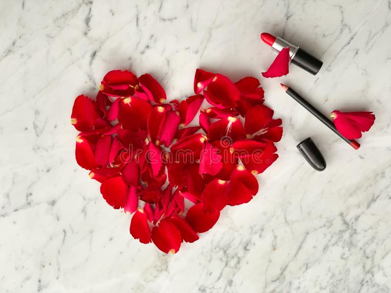 Pétalos color de rosa rojos en forma del corazón con la barra de labios roja en el fondo tablero de mármol, visión superior Ideas foto de archivo libre de regalías