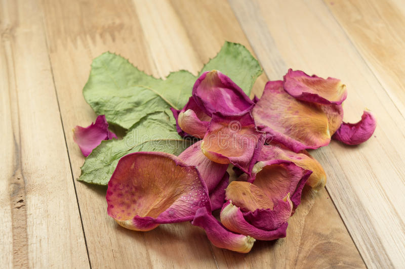 Pétalos color de rosa secados en la madera fotografía de archivo