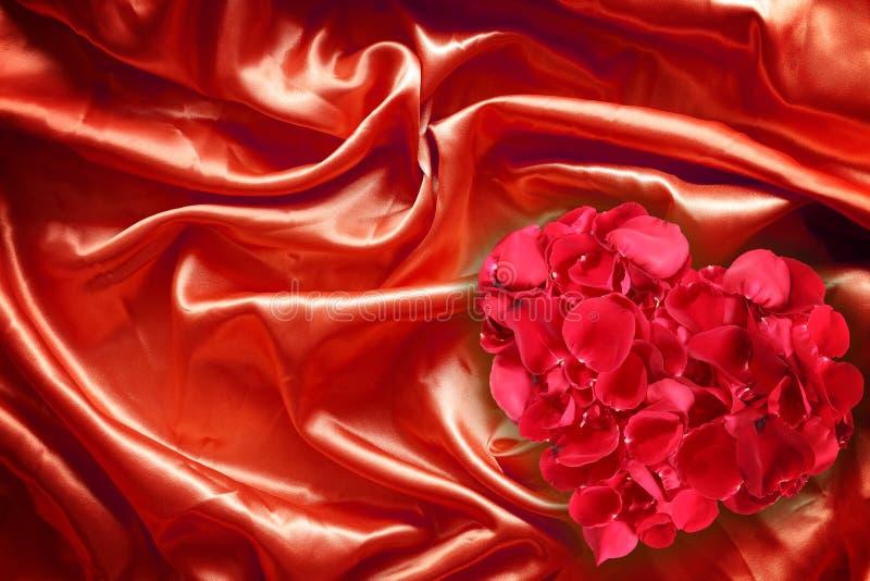 Pétalos de Rose en la seda roja de la tela fotos de archivo libres de regalías