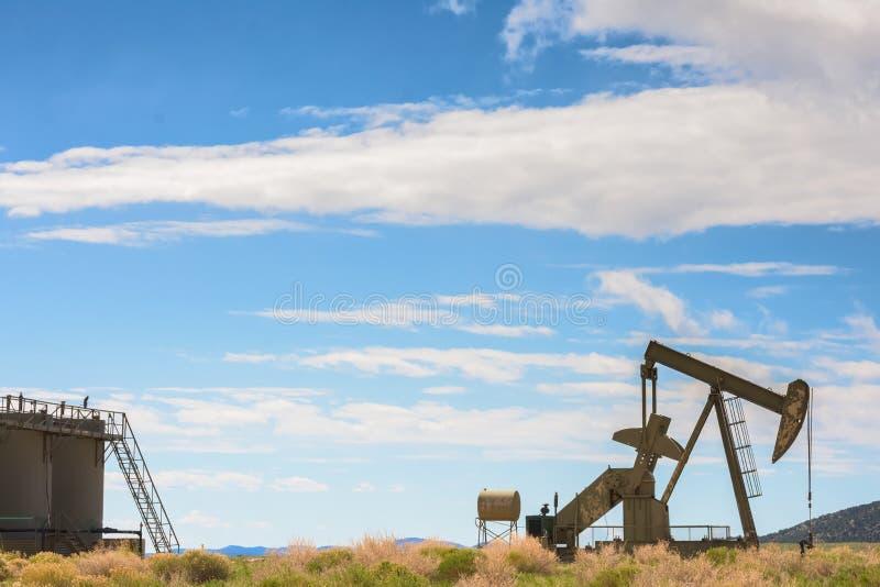 P?trole le puits et ?chouez contre les montagnes et le ciel nuageux bleu photos stock