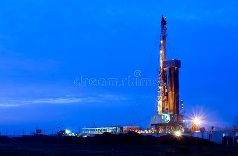 Pétrole puits la nuit images stock