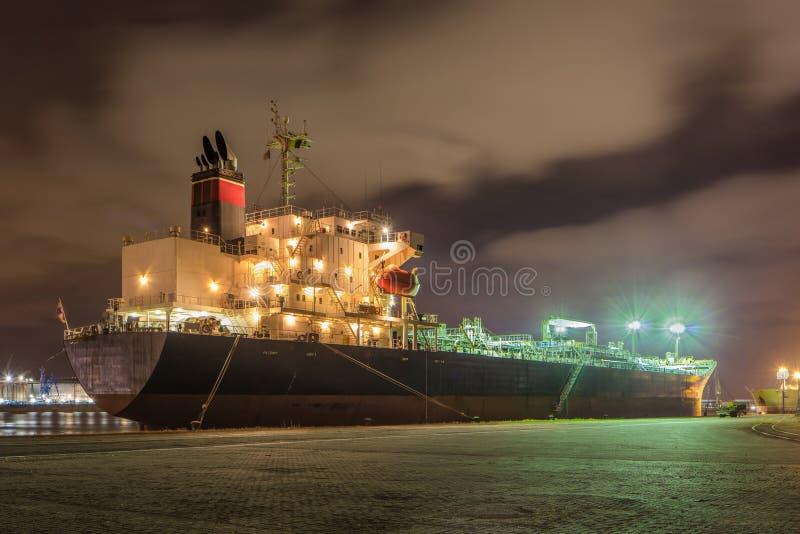 Pétrolier amarré la nuit avec les nuages dramatiques, port d'Anvers, Belgique images stock