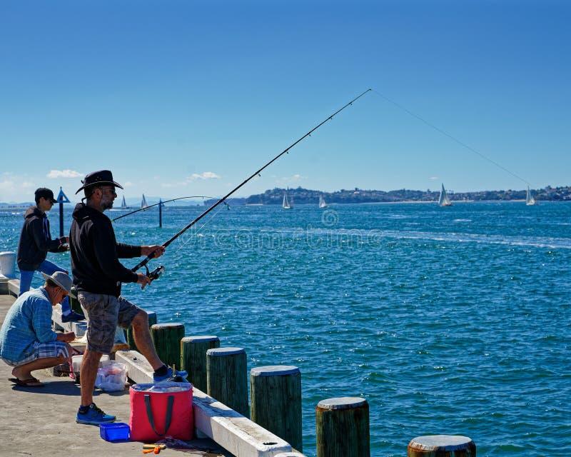Pêchant outre du pilier chez Devonport, Auckland, Nouvelle-Zélande image libre de droits