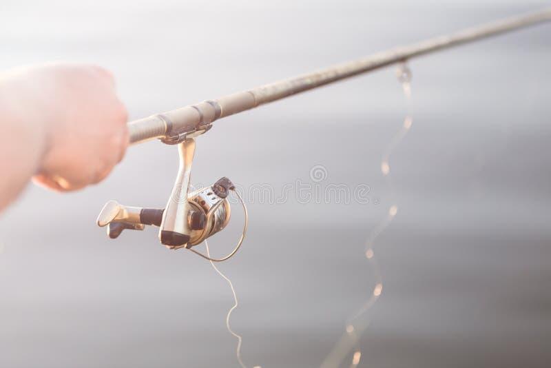 Pêche au lever de soleil Main en gros plan de pêcheur avec la canne à pêche de rotation Matin d'été sur la rivière ou le lac Copy photo stock
