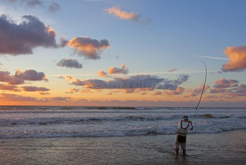 Pêche au surfcasting au coucher du soleil photos stock