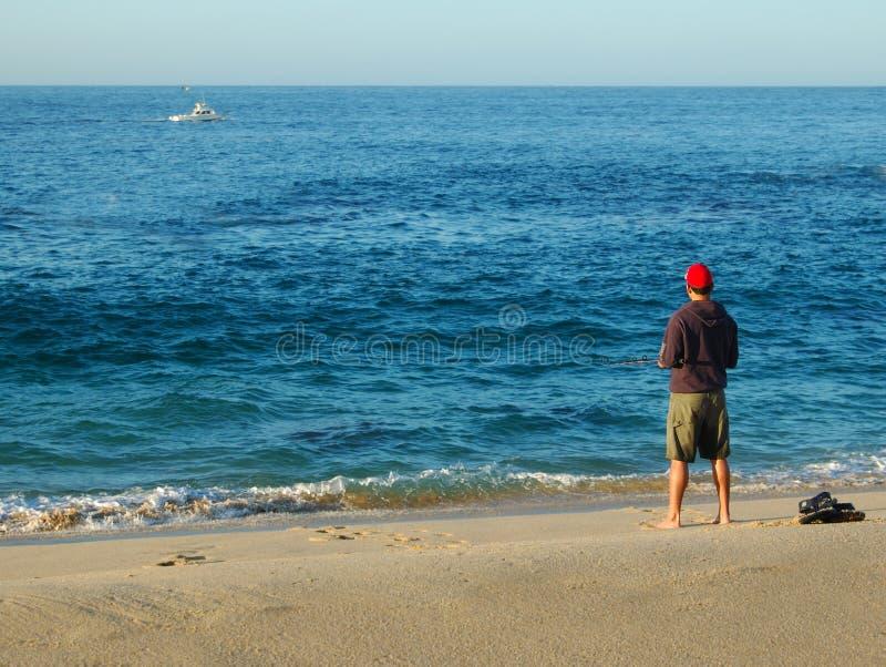 Pêche au surfcasting d'homme sur l'océan bleu bleu image libre de droits