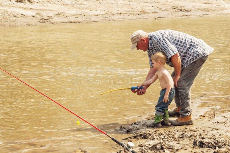 Pêche avec le grand-papa sur la rive boueuse photos stock